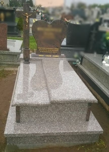Nagrobek wykończony szarym kamieniem z czerwono-czarnym pomnikiem