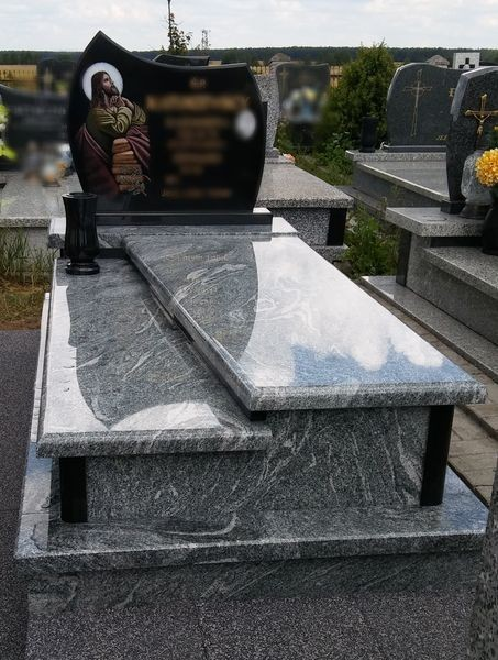 Nagrobek wykończony szarą płytą z czarnym pomnikiem